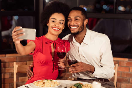 Photo pour Valentines Selfie. Happy African American Couple Making Self-Portrait On Smartphone Holding Wine Glasses Having Date In Restaurant - image libre de droit