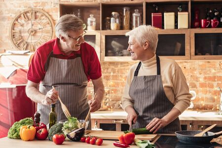 Photo for Happy retirement. Cheerful senior couple cooking healthy lunch together at home kitchen - Royalty Free Image