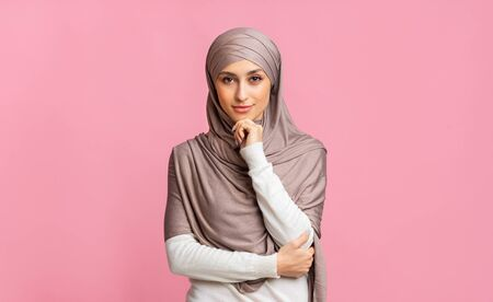 Photo pour Modern muslim woman. Portrait of confident islamic girl in hijab touching her chin and looking at camera, pink background with free space - image libre de droit