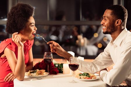 Photo for Romantic Date. Happy Afro Couple Feeding Each Other Having Dinner Celebrating Valentines Day In Restaurant - Royalty Free Image