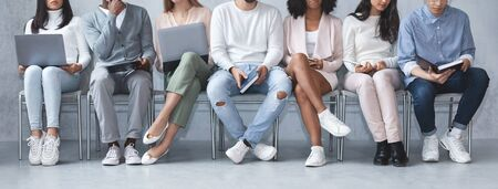 Photo pour Cropped image of young multiracial people with laptops and books sitting in line, waiting for job interview, panorama - image libre de droit