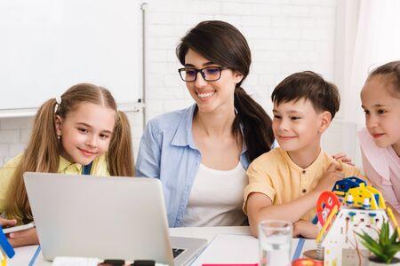 Photo pour Stem lesson. Pupils and teacher watching robotics video on laptop, studying at after school class - image libre de droit