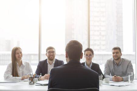 Photo pour Male applicant talking at job interview to hr comission, back view, free space - image libre de droit