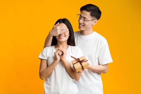 Cheerful asian guy making surprise to his excited girlfriend, covering her eyes, holding gift boxの写真素材