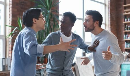 Photo for Office conflict. Angry multiracial young men fighting at workplace, afro guy standing between them - Royalty Free Image