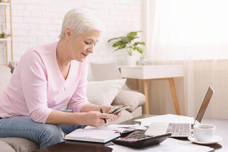 Photo pour Retirement savings. Senior lady counting money at home, empty space - image libre de droit