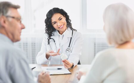 Visiting Doctor. Smiling latina physician showing mature couple pills, pointing at plastic bottle, giving prescription