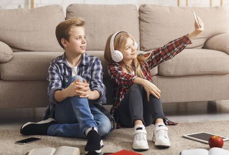 Photo for Best Friends. Boy And Girl Making Selfie On Smartphone Having Fun With Gadgets Sitting On Floor At Home On Weekend. - Royalty Free Image
