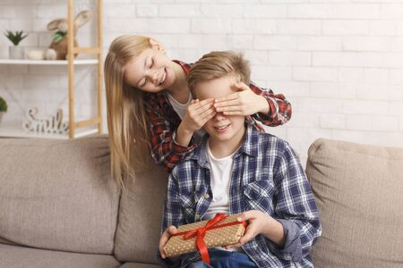 Foto de Sister Covering Brothers Eyes Congratulting Him And Giving Birthday Gift Sitting On Sofa At Home. Holidays And Presents Concepts. - Imagen libre de derechos