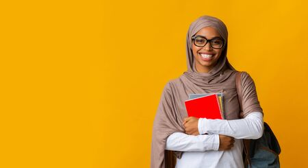 Photo pour Modern islamic education. Smiling afro muslim female student in headscarf and eyeglasses holding notebooks and looking at camera, yellow background - image libre de droit