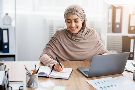 Photo pour Time Management At Work. Smiling Islamic Female Employee Using Laptop And Writing Notes, Managing Her Business Schedule In Office - image libre de droit
