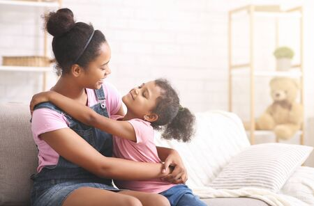 Photo pour Family love. Cheerful african sisters hugging at home, empty space - image libre de droit