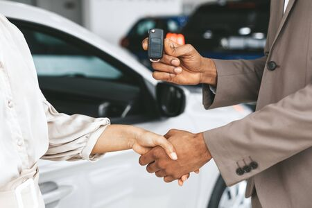 Photo pour Car Sales. Unrecognizable Seller Greeting Lady Buyer With Handshake And Giving Key Standing Near Automobile In Dealership Store. Cropped - image libre de droit