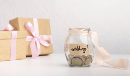 Photo pour Cash money coins in glass jar with text written for wedding over gray background, panorama, concept of saving or planning budget for wedding day - image libre de droit