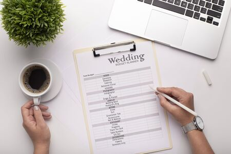 Foto de Woman planning her wedding, calculating budget and searching services on laptop, white table background - Imagen libre de derechos