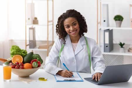Photo pour Cheerful afro woman dietologist working with laptop in modern office, having fresh juice, fruits and vegetables on table - image libre de droit