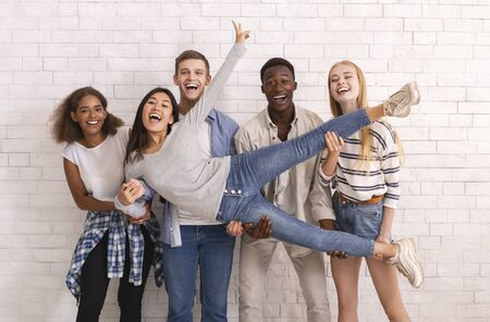 Photo pour Joyful international group of students lifting asian girl up, having fun over white wall background - image libre de droit