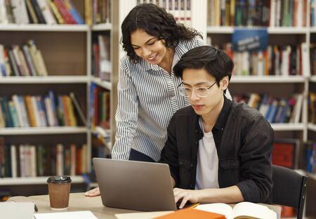 Photo for Academic Advisor. Female brazilian counselor monitoring work of korean architect student who using laptop in library - Royalty Free Image