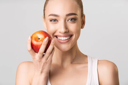 Photo for Strong Healthy Teeth. Woman With Perfect White Smile Holding Red Apple Posing Looking At Camera On Gray Studio Background. - Royalty Free Image