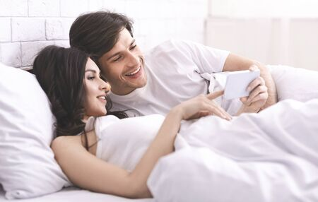 Photo pour Happy memories. Young married couple watching photos on cellphone, resting in bed - image libre de droit