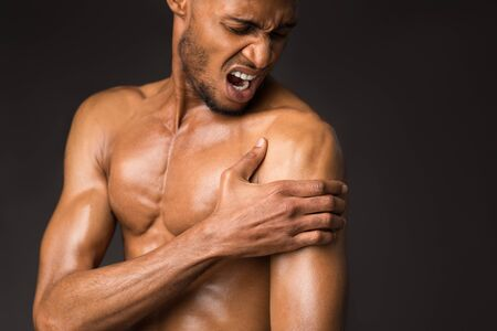 Photo pour Pain In The Shoulder. Muscular black bodybuilder suffering from pain touching his arm after sports injury, copyspace - image libre de droit