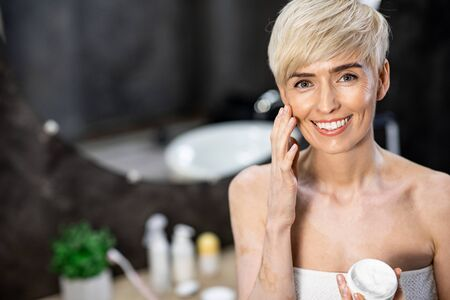 Photo for Facial Skin Care. Middle-Aged Woman Applying Cream On Face Holding Cosmetic Product Jar Smiling To Camera Standing In Bathroom. Copyspace - Royalty Free Image