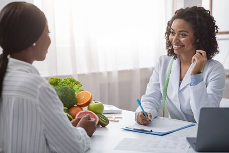 Photo pour Smiling african woman nutritionist talking to female patient and taking notes, clinic interior, appointment at dietologist - image libre de droit