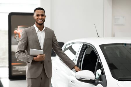 Photo pour Car Sales. Black Salesman Selling And Showing New Car Standing In Luxury Dealership Center. Selective Focus, Empty Space - image libre de droit