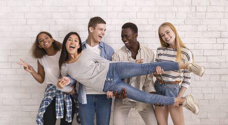 Photo pour Joyful international group of teenagers lifting asian girl up, having fun over white brick wall background, panorama - image libre de droit