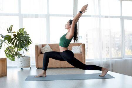 Foto für Healthy lifestyle and sports concept. Attractive Hispanic woman enjoying her morning yoga indoors. Warrior pose - Lizenzfreies Bild