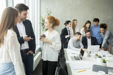 Photo for Young businesspeople sharing ideas and having friendly conversation at coffee break in office - Royalty Free Image