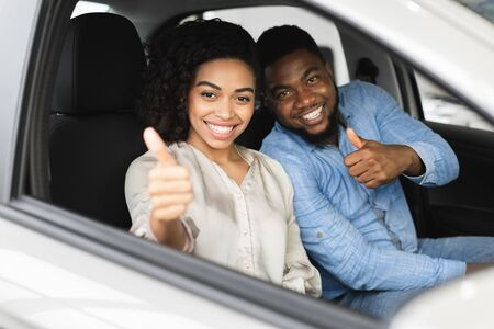Photo for Great Car. Happy Afro Couple Gesturing Thumbs Up Sitting In New Auto Buying Automobile In Dealership Store. Selective Focus - Royalty Free Image