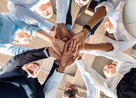 Photo for Business Unity And Teambuilding. United Colleagues Standing In Circle Holding Hands Together In Modern Office. Bottom View - Royalty Free Image