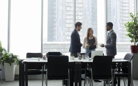 Foto de Coffee break. Businesspeople talking in front of office window after meeting, standing by table, empty space - Imagen libre de derechos