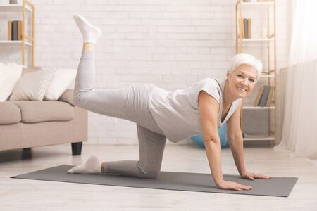 Photo for Senior fitness lady standing on all fours, straightening leg up, exercising at home - Royalty Free Image