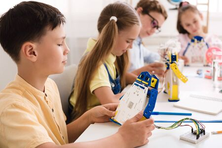 Photo pour Stem education. School boy working on project, making diy robot with classmates on background - image libre de droit