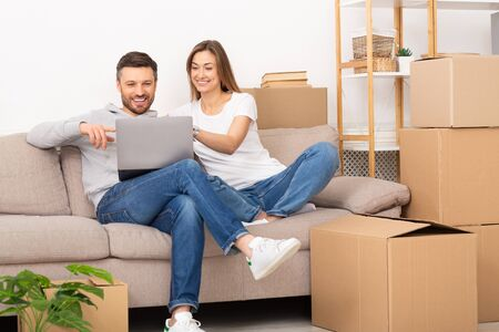 Foto für Young couple sit in new apartment with laptop, discuss home repair project in living room with sofa and stack of boxes. Moving and relocation concept. - Lizenzfreies Bild