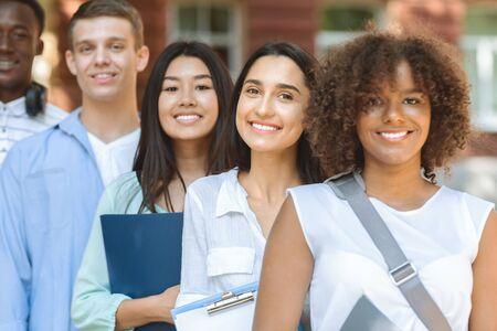 Photo pour Modern Student Community. Closeup Portrait Of Multi-Ethnical Teens Posing Outdoors Against University Building Background - image libre de droit