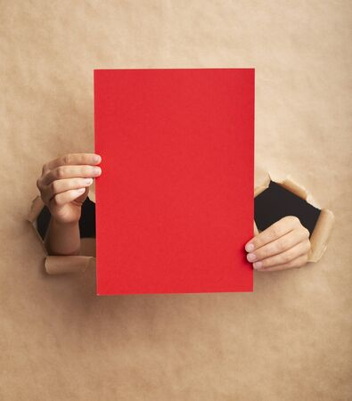 Photo pour Unrecognizable young lady holding red sheet with empty space through ripped craft paper - image libre de droit
