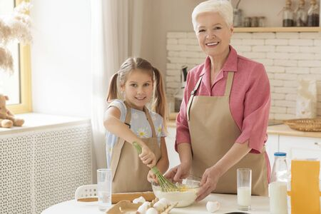 Photo pour Cooking time. Happy granny and her granddaughter baking togeher in kitchen, copy space - image libre de droit