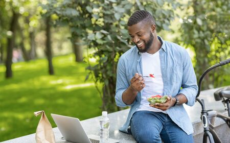 Photo pour Lunch Fun. Young Black Guy Eating Takeaway Salad Outdoors And Watching Videos On Laptop, Relaxing On Bench In Park - image libre de droit