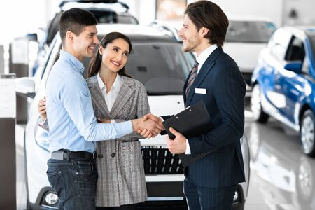 Photo pour Pleasure Working With You. Beautiful couple embracing after buying new car, shaking hands with salesman - image libre de droit
