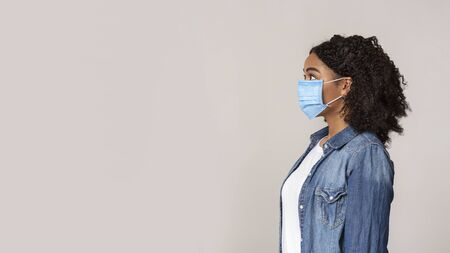Photo pour Profife portrait of scared african american woman wearing protective medical mask and looking aside at copy space on light studio background, panorama - image libre de droit