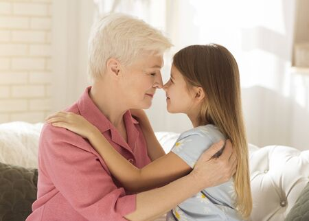 Photo pour Family happiness concept. Lovely little girl and her grandma touching noses and embracing at home - image libre de droit