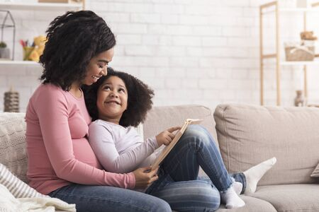 Foto de Preschool Development Concept. Little Black Girl Reading Book With Her Pregnant Mom At Home, Sitting On Couch And Smiling, Copy Space - Imagen libre de derechos