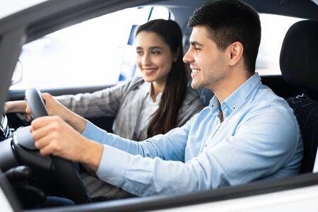 Photo pour Enjoying Travel. Young couple sitting in brand new car, testing their new rental transport - image libre de droit