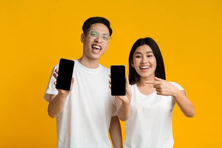 Photo pour Cheerful asian couple showing their smartphones with blank screens, yellow background - image libre de droit