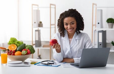 Photo pour Attractive woman doctor sitting at dietologist workplace in front of laptop, kindly recommending eating fresh fruits, free space - image libre de droit