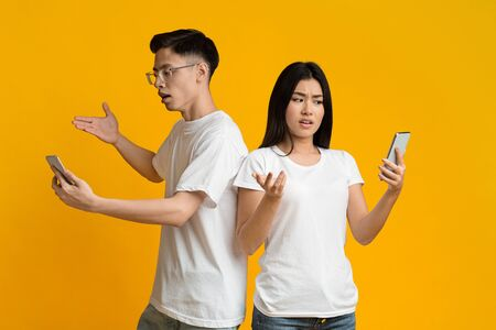 Photo pour Troubles with communication. Confused asian man and woman looking at their mobile phones over yellow background - image libre de droit