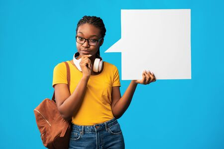 Photo for Thoughtful Black Student Girl Showing Empty Speech Bubble Thinking About Something Posing Over Blue Studio Background. Mockup - Royalty Free Image